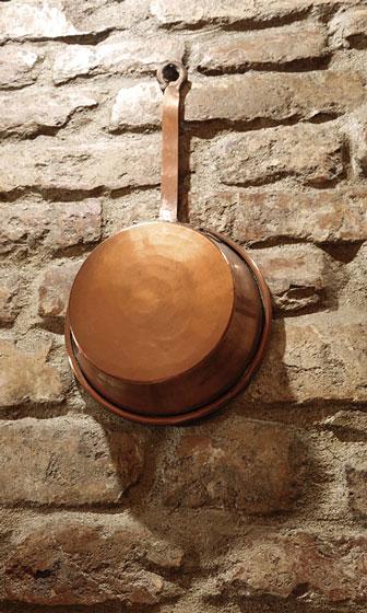 antique copper pot hanging on a brick wall