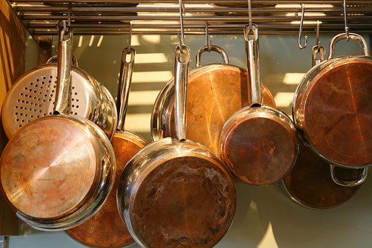 copper saucepans hanging from a rack